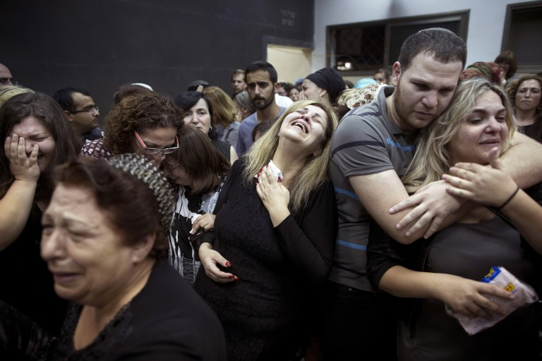 """FILE - In this Saturday, June 20, 2015 file photo, friends and relatives of Danny Gonen mourn next to his body during his funeral, at the cemetery in the city of Lod, near Tel Aviv, Israel. Gonen was killed when a gunman opened fire at a car outside a West Bank settlement on Friday, killing an Israeli man and wounding another in what police said was a """"terror attack."""" The Palestinian militant group Hamas praised the attack but stopped short of claiming responsibility. (AP Photo/Oded Balilty, File)"""